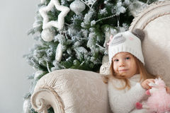 Child girl with sheep toy and Christmas tree Stock Photos