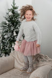 Child girl with sheep toy jump at couch near Christmas tree Royalty Free Stock Photos