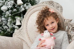 Child girl with sheep toy sits near Christmas tree royalty free stock image