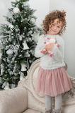 Child girl with sheep toy stand near Christmas tree Royalty Free Stock Photography