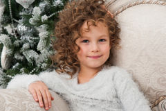 Child girl sit on couch, Christmas tree Stock Photos