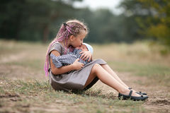 Child girl sits on grass with her newborn brother on walk in par royalty free stock photos