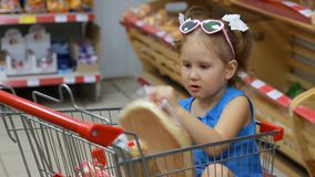 Child girl sits in a trolley for food in the supermarket and holds a bread. Baby shopping. Child girl sits in a trolley for food in the supermarket and holds a stock video footage