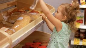 Child girl sits in a trolley for food in the supermarket and holds a bread or pita. Baby shopping stock footage