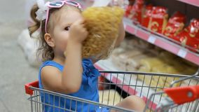 Child girl sits in a trolley for food in the supermarket and holds a pasta. Baby shopping.  stock video footage