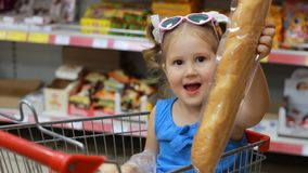 Child girl sits in a trolley for products in the store and holds a baguette. Baby shopping.  stock video