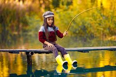 Child girl sits on wooden fishing bridge and catches fish in aut. Child girl sits on wooden fishing bridge and catches fish with self-made fishing rod in autumn royalty free stock photos
