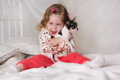Child girl is sitting on bed at home with dog Royalty Free Stock Photography