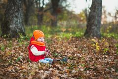 Child girl sitting on the grass in the autumn park and holding an apple in his hands royalty free stock image