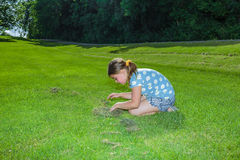 Child girl sitting  and looking down on grass field Stock Photos