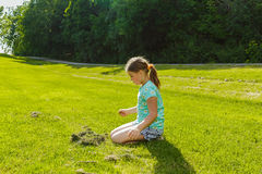 Child girl  sitting and looking down on green grass field Stock Photo