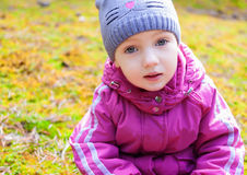 Child girl sitting moss thoughtful look Royalty Free Stock Photography