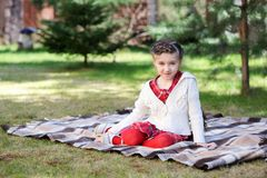 Child girl sitting on plaid in a garden Royalty Free Stock Image