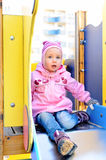 Child girl sitting on slide Royalty Free Stock Photography
