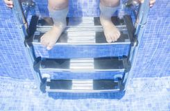 Child girl sitting on the swimming pool ladder with legs underwa. Ter. Children summer concept Royalty Free Stock Photography