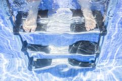 Child girl sitting on the swimming pool ladder with legs underwa. Ter. Children summer concept Stock Photos