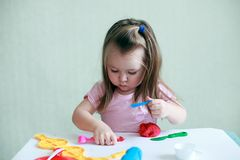 Child girl sitting at table playing with colorful clay indoor, concept of preschool education and art therapy stock image