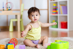 Child girl sitting among toys on carpet at home Stock Image