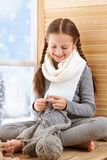 Child girl is sitting on a window sill and knitting the scarf from gray wool yarn. Beautiful view outside the window - sunny day royalty free stock photos