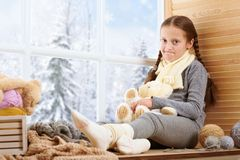 Child girl is sitting on a window sill and playing with bear toy. Beautiful view outside the window - sunny day in winter and snow royalty free stock images