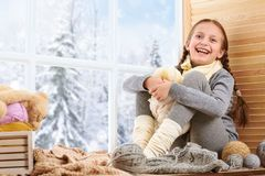 Child girl is sitting on a window sill and playing with bear toy. Beautiful view outside the window - sunny day in winter and snow royalty free stock photos