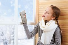 Child girl is sitting on a window sill and playing with handmade mitten. Beautiful view outside the window - sunny day in winter. And snow royalty free stock image