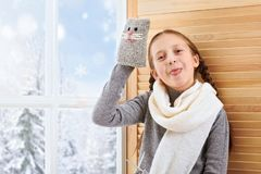 Child girl is sitting on a window sill and playing with handmade mitten. Beautiful view outside the window - sunny day in winter stock photos