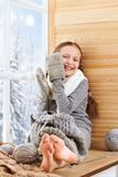 Child girl is sitting on a window sill and playing with handmade mitten. Beautiful view outside the window - sunny day in winter royalty free stock image