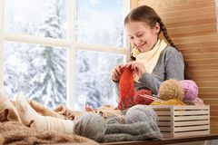 Child girl is sitting on a window sill with wool yarns and knitting. Beautiful view outside the window - sunny day in winter and stock photo