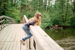 Child girl sitting on a wooden bridge near the water on the rive Stock Photo