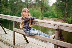 Child girl sitting on a wooden bridge near the water Royalty Free Stock Images