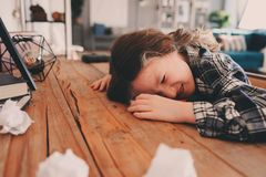 Child girl sleeping while doing homework. School kid learning hard and get tired. Papers with mistakes are around. Education problems and overworking concept stock images