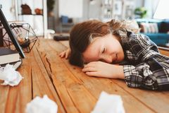 child girl sleeping while doing homework. School kid learning hard and get tired, papers with mistakes around. Education probl Royalty Free Stock Photography