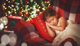 Child girl is sleeping near a Christmas tree Royalty Free Stock Image
