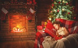 Child girl is sleeping near a Christmas tree Stock Photos