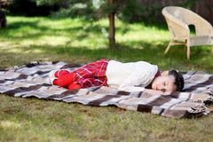 Child girl sleeping on plaid in a garden Royalty Free Stock Image
