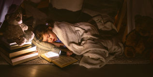 Child girl sleeping in tent with  book and flashlight Royalty Free Stock Images