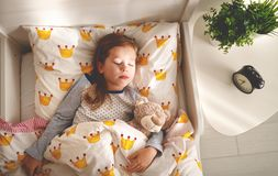 Child  girl sleeps in her bed with toy teddy bear  in morning Royalty Free Stock Photo