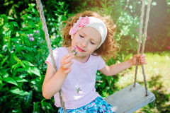 Child girl smells flower on swing in summer garden Royalty Free Stock Photography