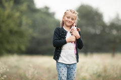 Child girl smiles and plays with her doll on walk. Stock Image