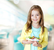 Child girl smiling carry plate salad in cafe background. Royalty Free Stock Images