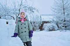 Child girl with snow castle on snowy winter backyard Stock Image
