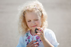 Child girl squinted and looks at the pebble Stock Images