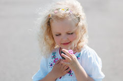 Child girl squinted and looks at the pebble Stock Photography