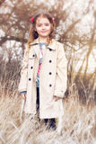 Child girl standing outdoors in coat vintage style. Royalty Free Stock Photos