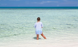 Child girl standing in tranquil, turquoise beautiful inviting ocean and feeding the fish Stock Photo