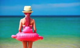 Child girl stands with her back with a Flamingo lifeline on beach. On sea royalty free stock image
