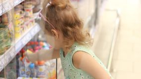 Child girl in the store opens the refrigerator door and buys baby food. Shopping in the supermarket.  stock video