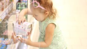 Child girl in the store opens the refrigerator door and buys baby food. Shopping in the supermarket.  stock footage