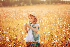 Child girl in straw playing with blow balls on summer field Royalty Free Stock Image